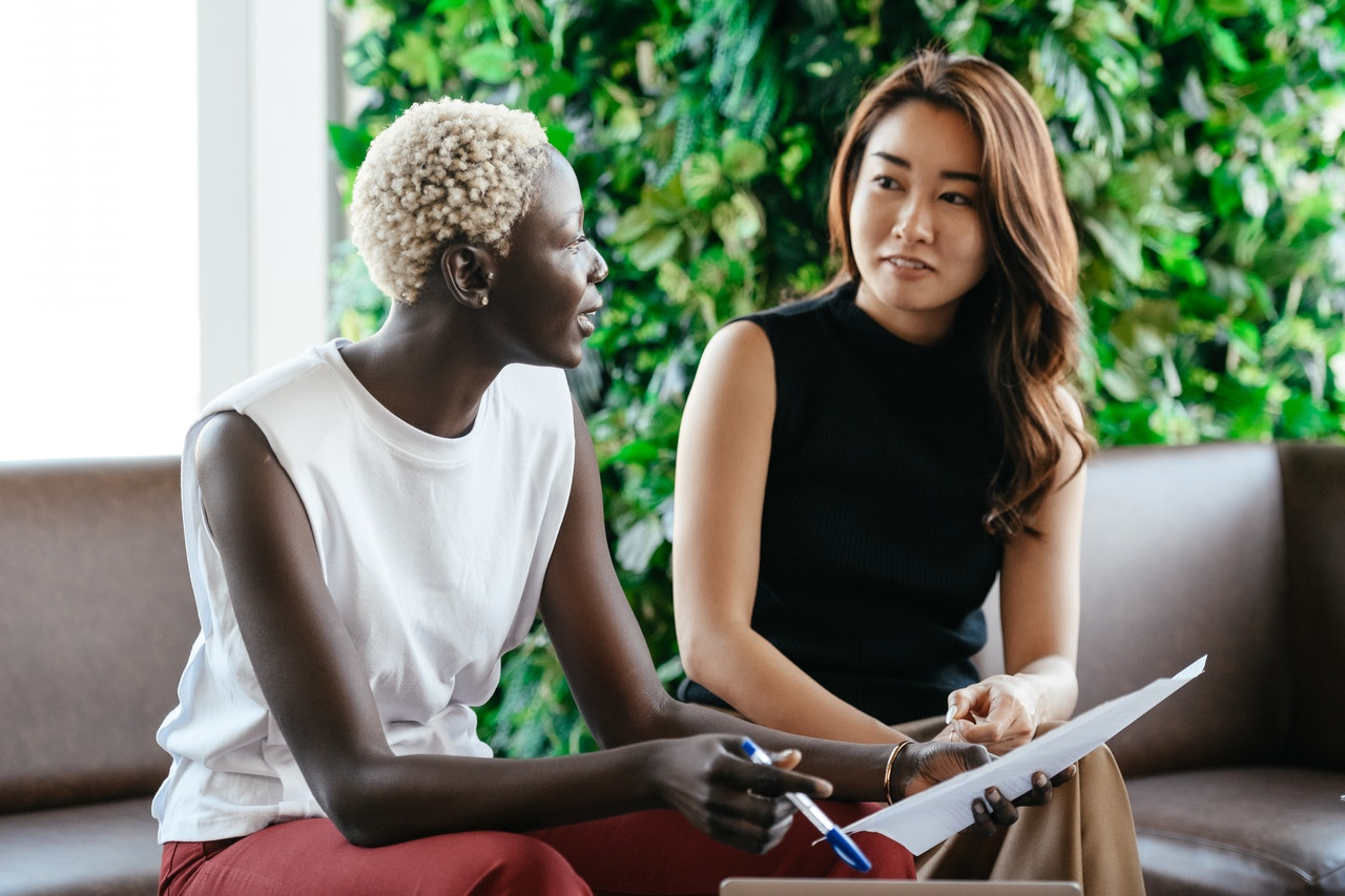 a Black woman and Asian woman in a business meeting
