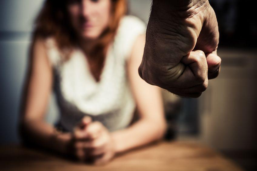 a woman fearing the balled up fist of a man in front of her