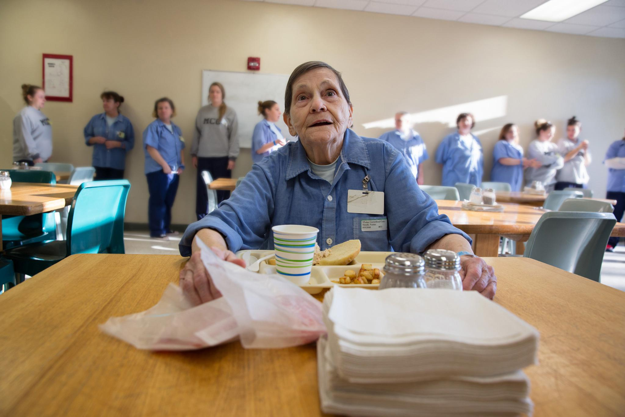 Elderly woman eating in prison