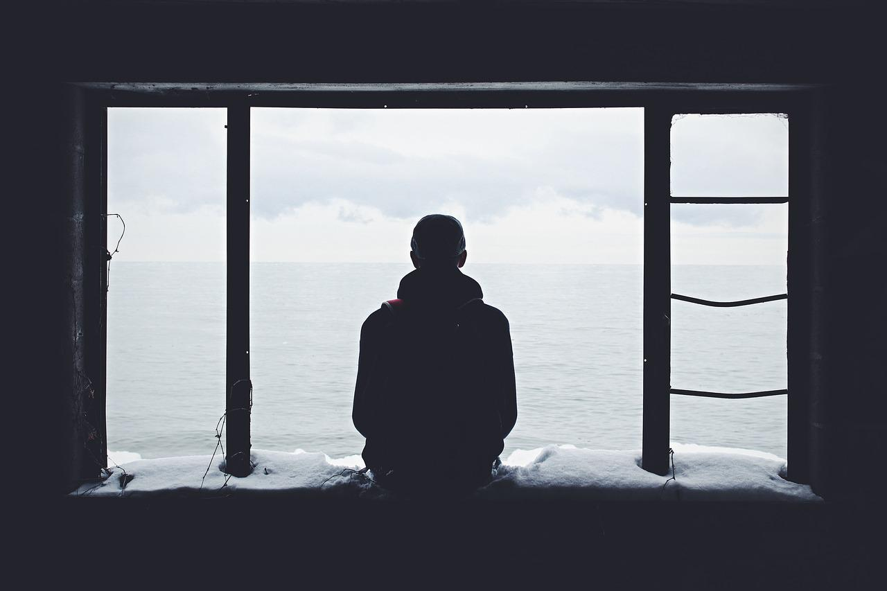 a man sitting in a window in solitude