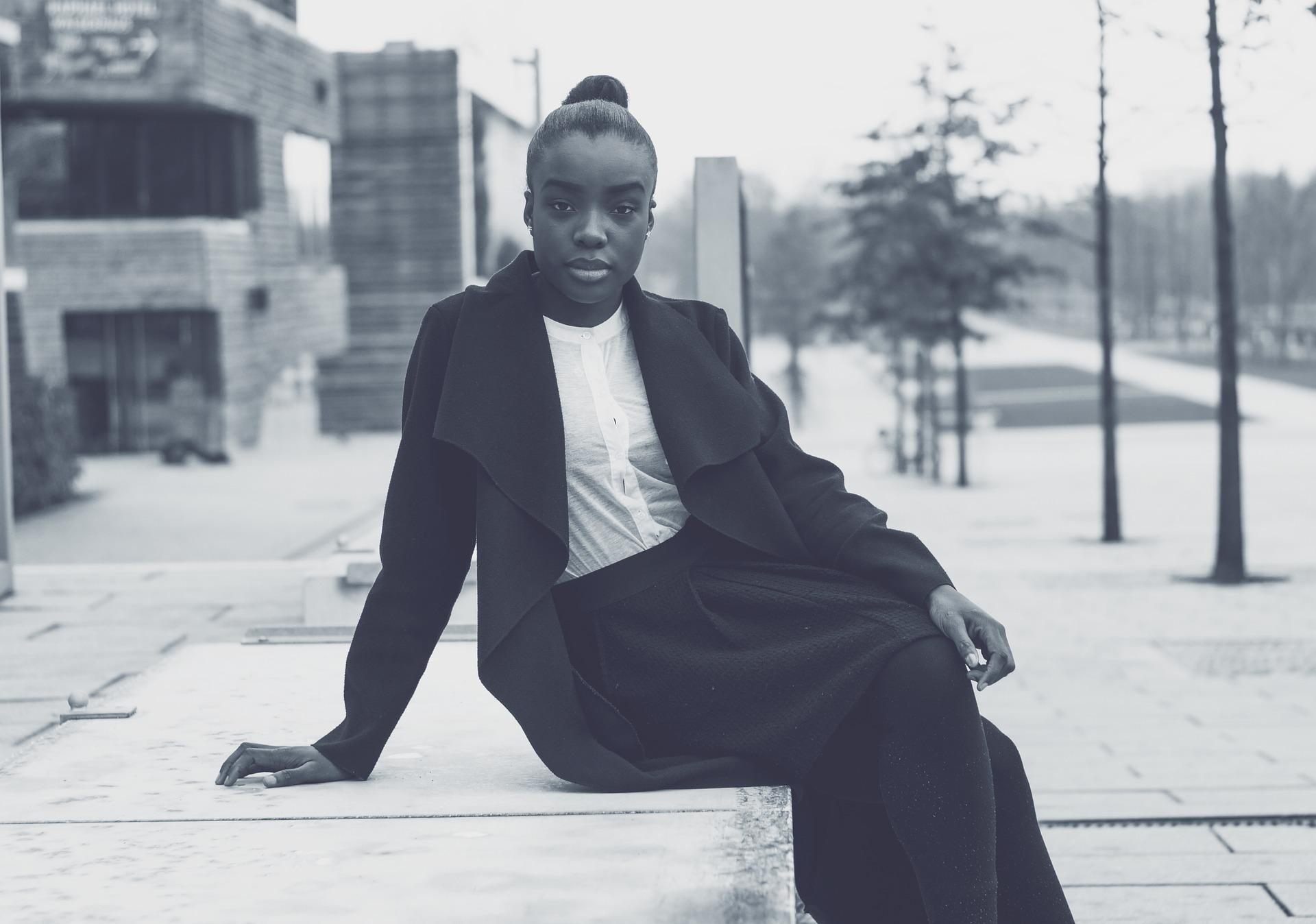 a young black woman sitting in the city
