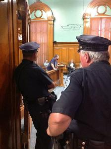 Jails division image of two officers looking into a court room