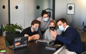 a team of people wearing masks, looking at one person's cell phone