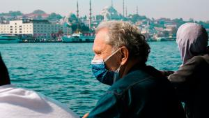 an older man wearing a mask, overlooking the water across from a city