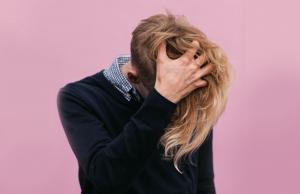 Gender neutral person with long blonde hair on a pink background